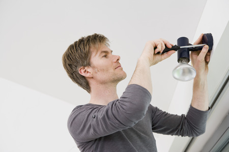 Man installing light fixture in house LANG_EVOIMAGES