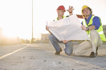 personas reunidas: Trabajadores de la construcción leyendo el modelo