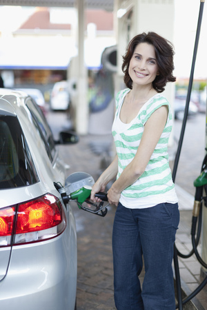 fillup: Woman pumping gas into car