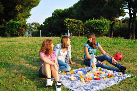 picnicking: Teenage girls picnicking in rural field