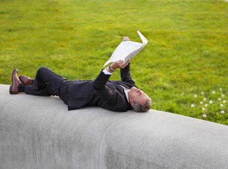 Businessman reading newspaper in park LANG_EVOIMAGES