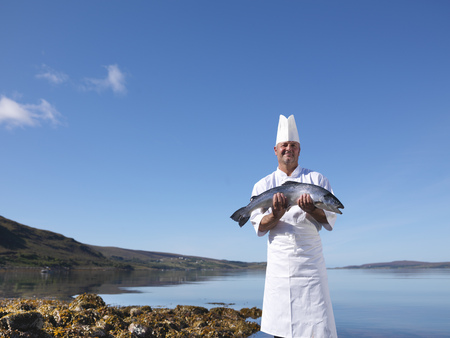 blue waters: Chef holding salmon by lake