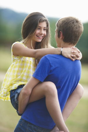 Teenage couple hugging outdoors