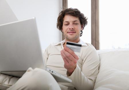 Man shopping online in living room LANG_EVOIMAGES