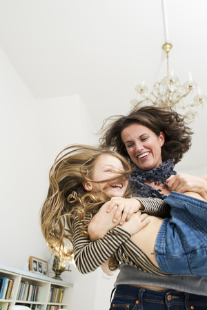 spirited: Woman playing with daughter in kitchen