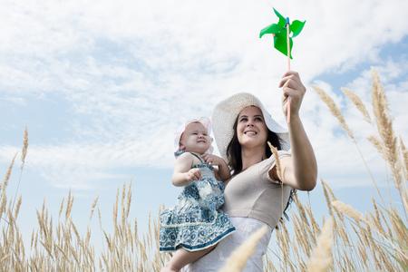 Woman holding pinwheel for daughter LANG_EVOIMAGES
