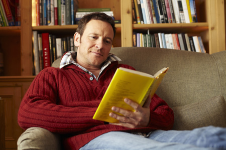 tomes: Man reading book on sofa