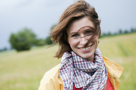wind blown: Smiling woman walking outdoors