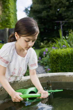 Girl filling up watering can in fountain