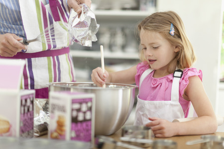 help section: Mother and daughter baking in kitchen
