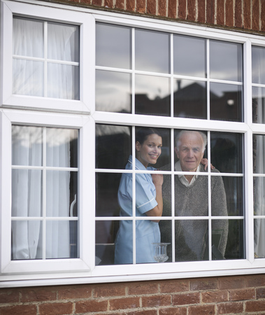 faiths: Nurse and older man at window