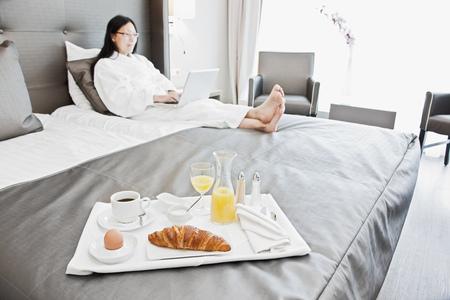 uses: Businesswoman having breakfast in bed