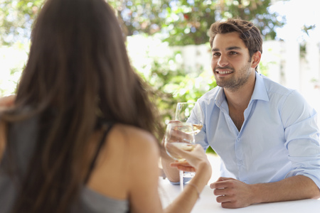 Couple having wine at table outdoors LANG_EVOIMAGES