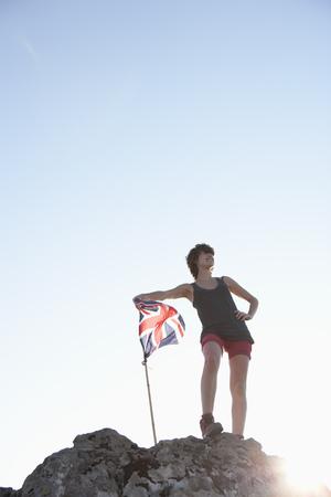 Hiker planting Union Jack flag LANG_EVOIMAGES