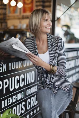 Woman reading newspaper at sidewalk cafe