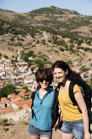 Women smiling together on hill LANG_EVOIMAGES