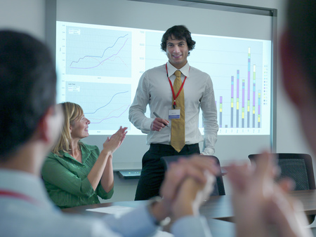 instructs: Business people applauding colleague