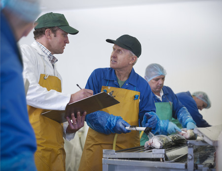 Workers talking in fish processing plant LANG_EVOIMAGES