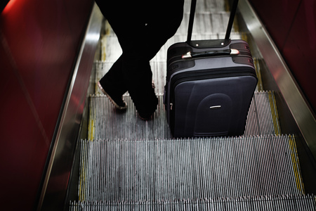 low section: Woman with luggage on escalator LANG_EVOIMAGES