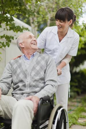 Nurse wheeling older patient outdoors
