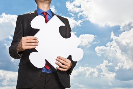strategize: Businessman holding puzzle piece