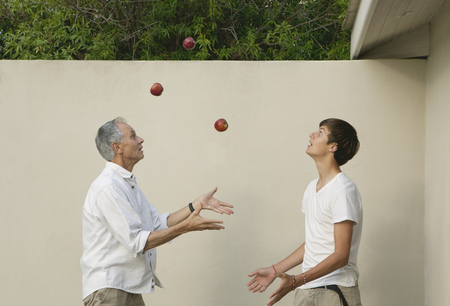 tosses: Father teaching son to juggle outdoors
