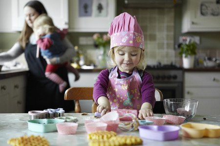 trusted: Toddler girl baking in kitchen