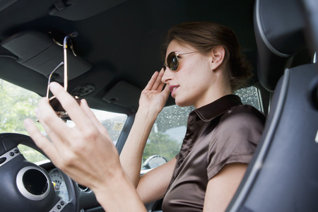 chic woman: Woman trying on sunglasses in car LANG_EVOIMAGES