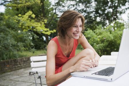 uses: Smiling woman using laptop in backyard