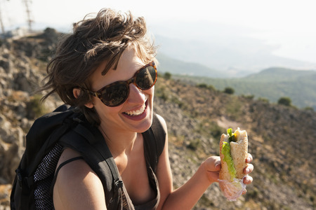 Hiker eating sandwich on hill
