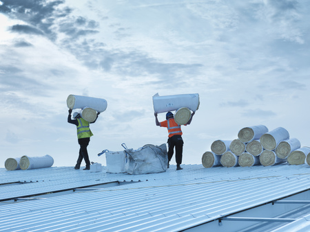 arms lifted up: Workers carrying insulation on roof