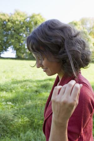 pelo castaño claro: Sonriente mujer caminando al aire libre