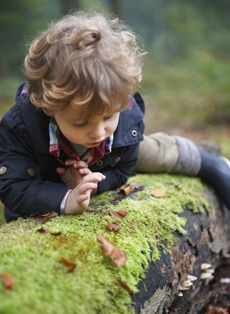 Toddler climbing on mossy log in park