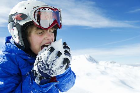 boca cerrada: Boy tasting snowball on mountain