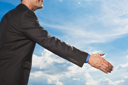 Businessman holding out hand to shake LANG_EVOIMAGES