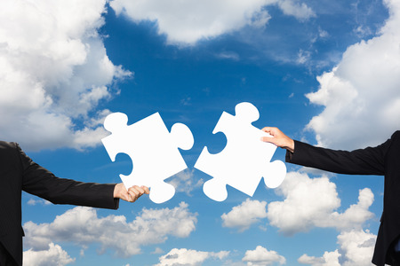 resourceful: Businesspeople holding puzzle pieces