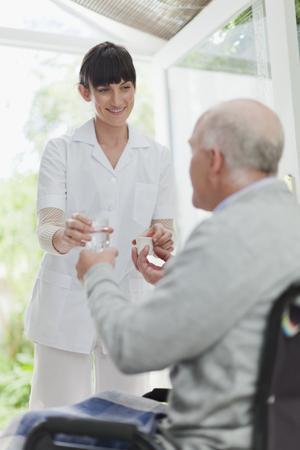 cures: Nurse giving older patient medication