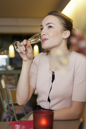 Smiling woman drinking champagne in cafe