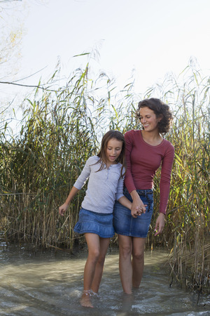 Mother and daughter walking in pond