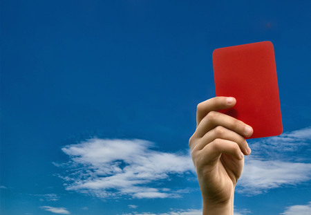 cautions: Hand holding red card against blue sky LANG_EVOIMAGES