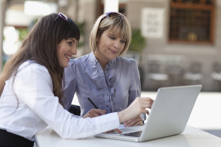 technology: Businesswomen working on laptop together