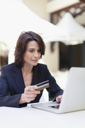 indebted: Businesswoman shopping online outdoors