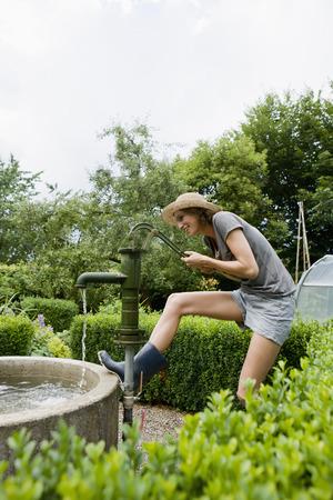 Smiling woman pumping water in backyard LANG_EVOIMAGES