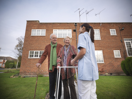 faiths: Nurse and older couple walking outdoors LANG_EVOIMAGES