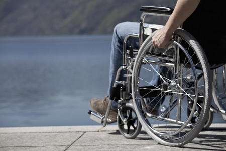jeopardizing: Man in wheelchair sitting by water