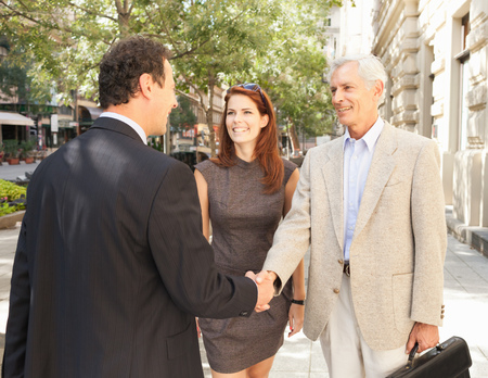 agrees: Business people shaking hands outdoors