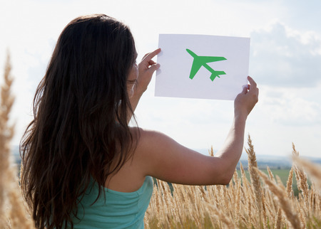 Woman holding picture of airplane in sky LANG_EVOIMAGES