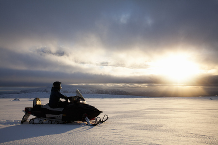 Man driving snowmobile in snowy field LANG_EVOIMAGES