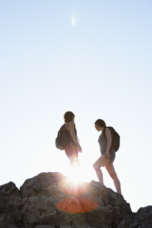 ceasing: Silhouette of hikers standing on rock
