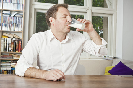 Man drinking glass of milk at table